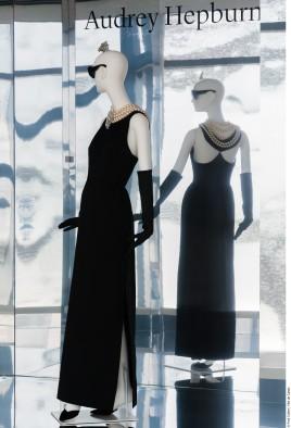Exposition Hubert de Givenchy, par la Cité de la Dentelle et de la Mode de Calais..Robe fourreau du soir en satin portée par Audrey Hepburn dans le film Diamants sur canapé de Blake Edwards. Hiver 1960. Collection Givenchy.